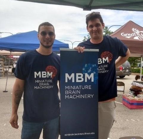 Jorge Maldonado De-Jesus (left) and Brian Baculis (right) share brain science outreach at the Urbana Farmer's Market, June 2019.